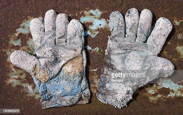Pair of badly worn work gloves on rusty metal plate