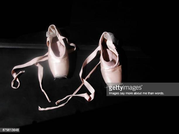 A pair of ballet shoes forgotten on a dark floor.