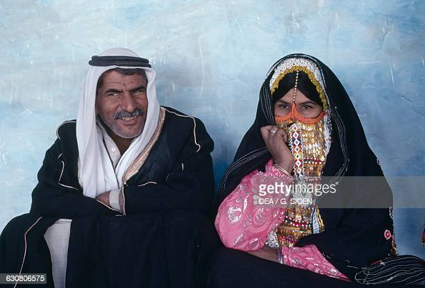 A pair of Bedouins the woman is wearing a niqab decorated with gold pendants Sinai Egypt