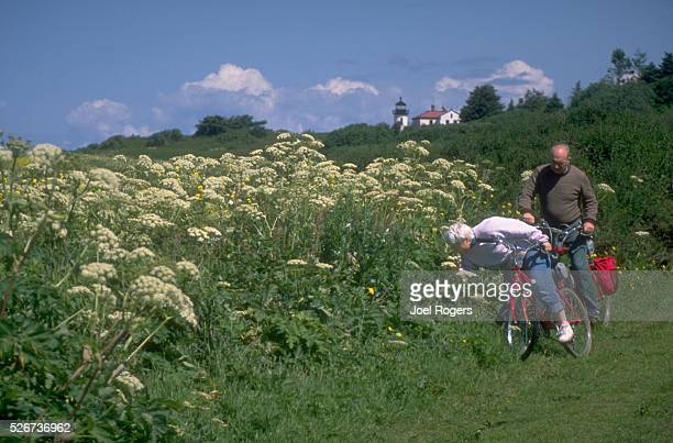 A pair of bicyclists stop to enjoy the local wildflowers along a trail near Fort Casey Park on Washington's Whidbey Island