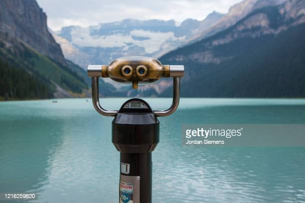 a pair of binoculars looking across lake louise. - canada stock pictures, royalty-free photos & images