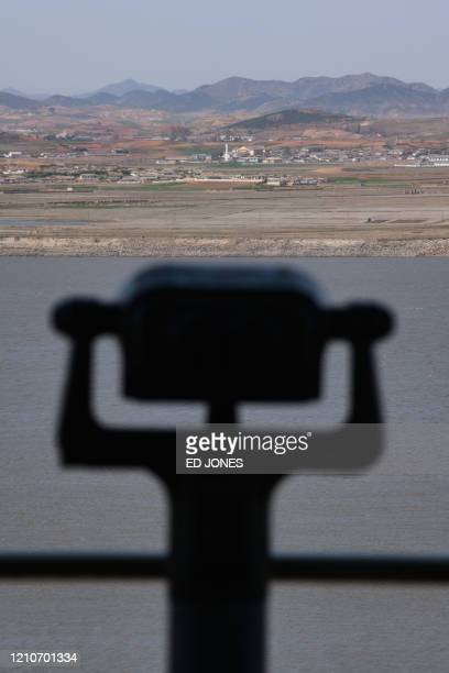 Pair of binoculars stands before the shoreline of North Korea and the Demilitarized Zone , on the South Korean island of Ganghwa on April 23, 2020. -...