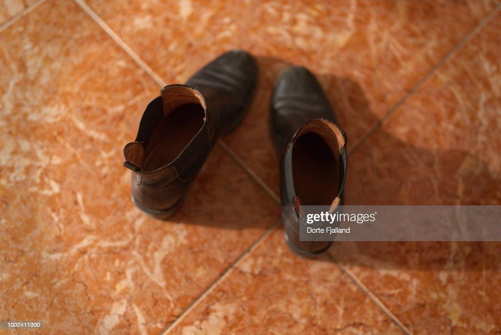 Pair of black boots on a tiled floor : Foto de stock