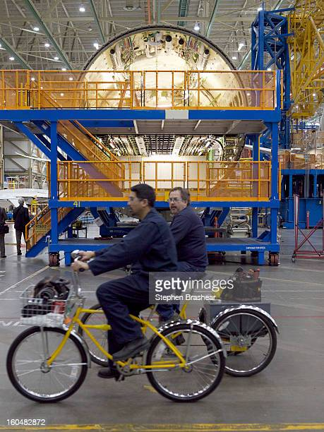 A pair of Boeing employees ride past a section of a Boeing 787 Dreamliner fuselage June 13 2012 at the Boeing Factory in Everett Washington