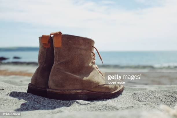 pair of boots on sandy beach - horizon over water stock pictures, royalty-free photos & images