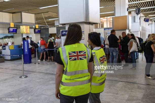A pair of British government officials stand in the main lounge of the Greek airport of Kalamata on September 23 one of several departure points for...