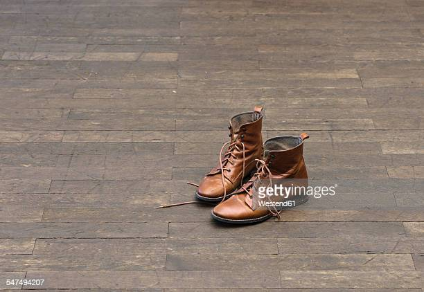 Pair of brown boots on wooden floor