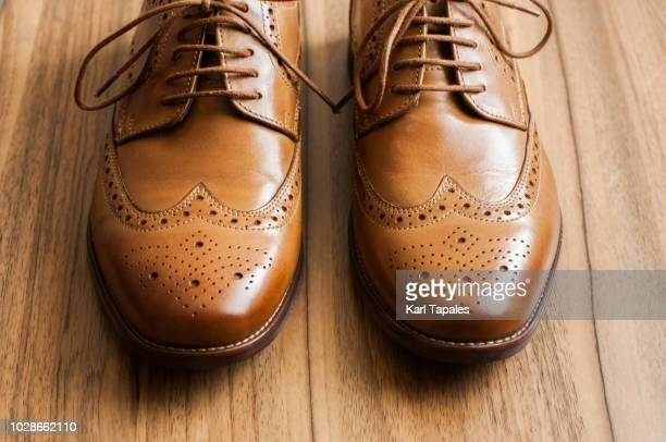 A pair of brown derby shoes with full brogue