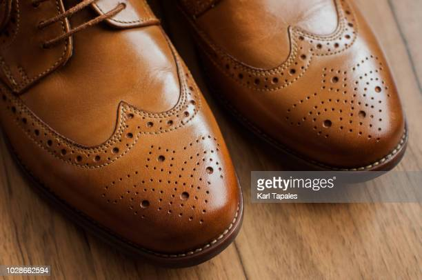 a pair of brown derby shoes with full brogue - brown shoe stock photos and pictures