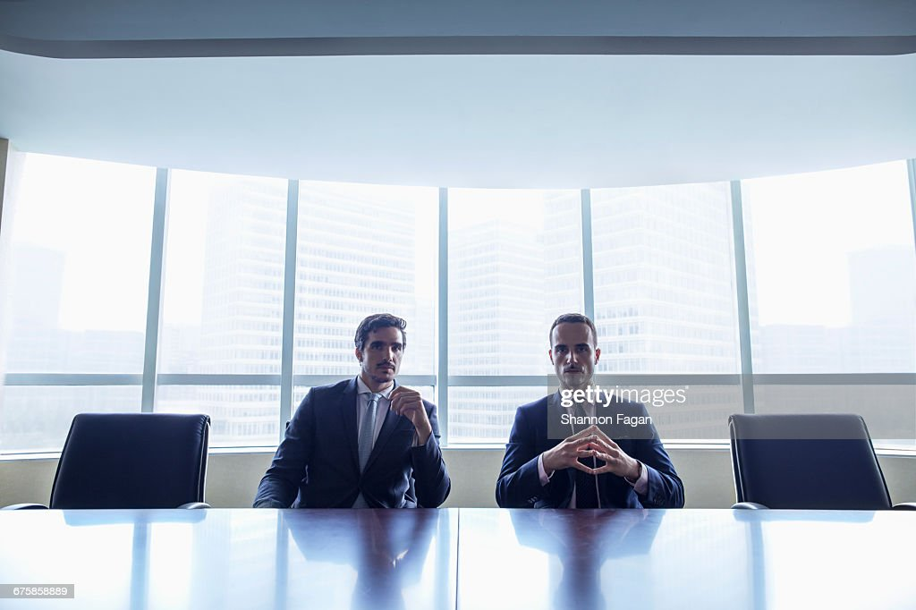 Pair of businessmen sitting at conference table : Stock-Foto