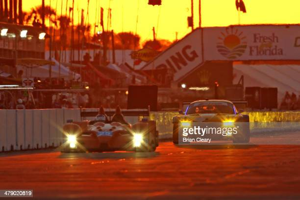 A pair of cars races down the frontstretch at sunset during the 12 Hours of Sebring at Sebring International Raceway on March 15 2014 in Sebring...