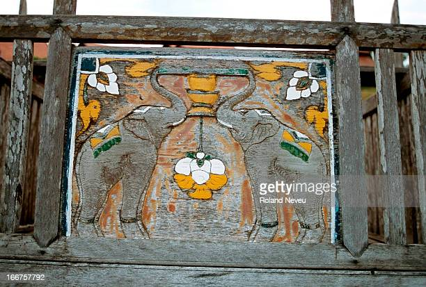 Pair of carved elephants adorns a wooden gate of a pagoda in a village of the north of Thailand..