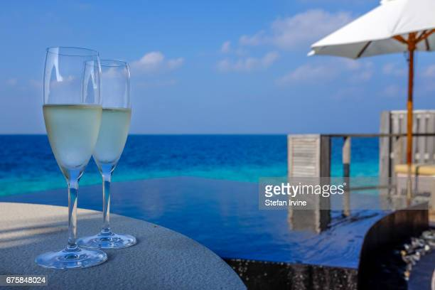 A pair of champagne glasses are set out poolside for a couple to enjoy on their private deck at a luxury resort in the Maldives