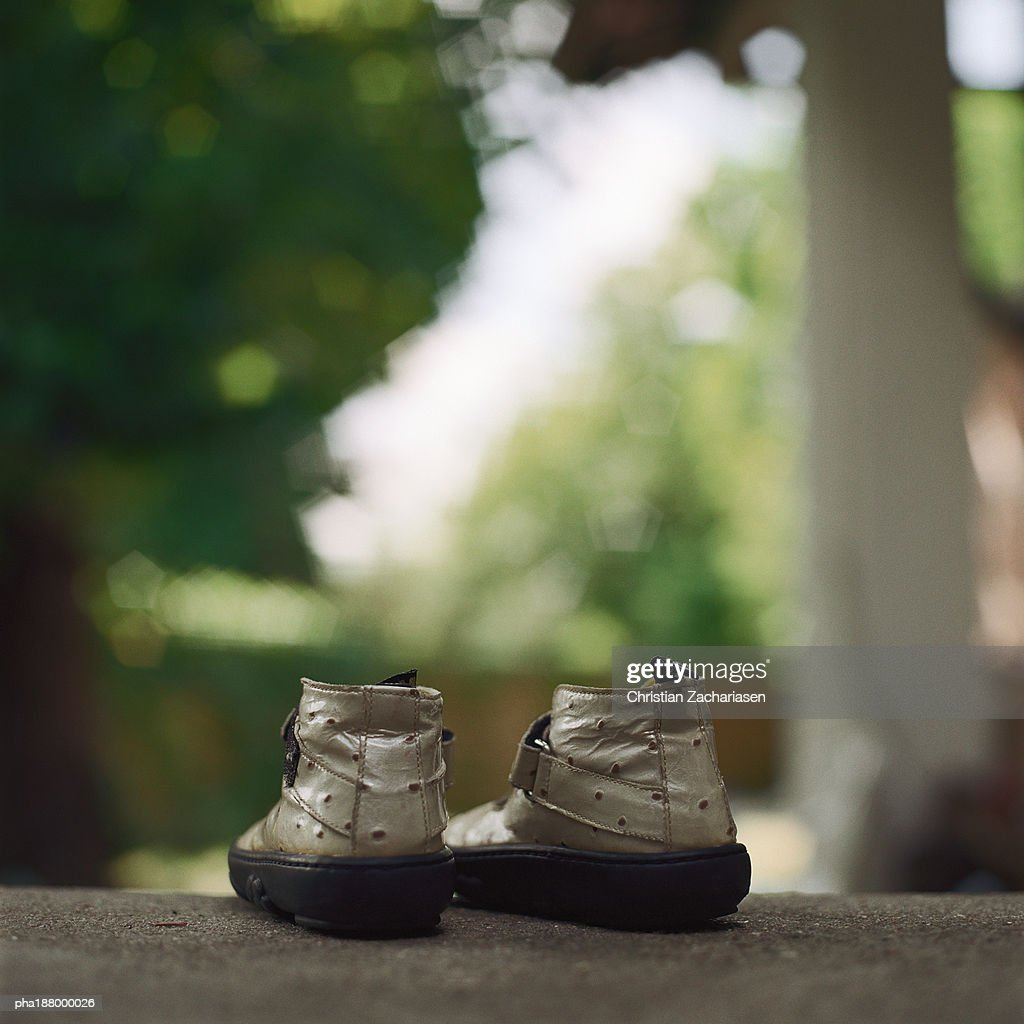 A pair of child's shoes sitting on ground. : Stockfoto