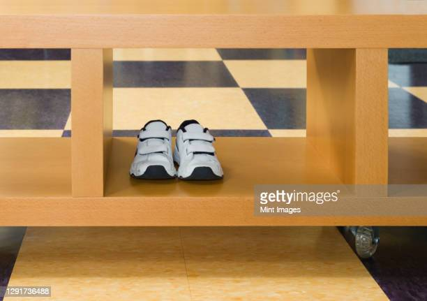 pair of child's trainers in rolling storage crate on tiled floor. - lino stock pictures, royalty-free photos & images