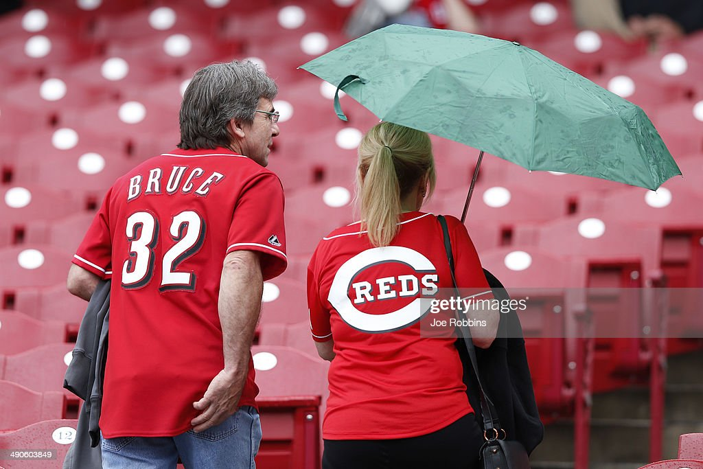 A pair of Cincinnati Reds fans head for the concourse as the start of the game against the San Diego Padres is delayed by rain at Great American Ball Park on May 14, 2014 in Cincinnati, Ohio.