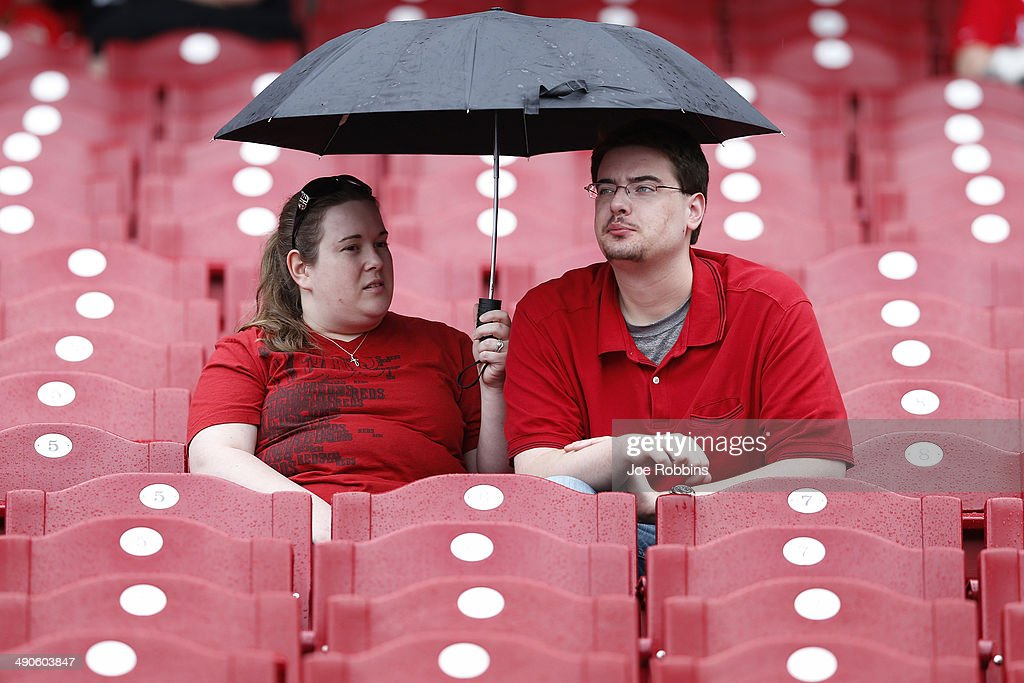 A pair of Cincinnati Reds fans sit in the rain as the start of the game against the San Diego Padres is delayed at Great American Ball Park on May 14, 2014 in Cincinnati, Ohio.