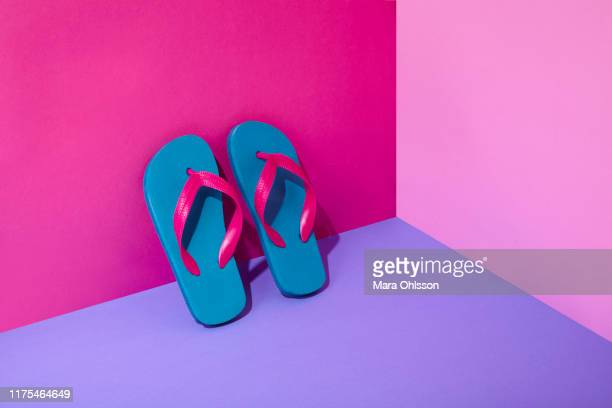 pair of colourful flip-flops leaning on wall - multi colored shoe stock pictures, royalty-free photos & images