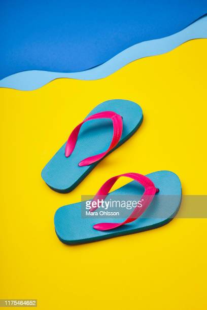 pair of colourful flip-flops on sandy beach by sea - yellow shoe stock pictures, royalty-free photos & images