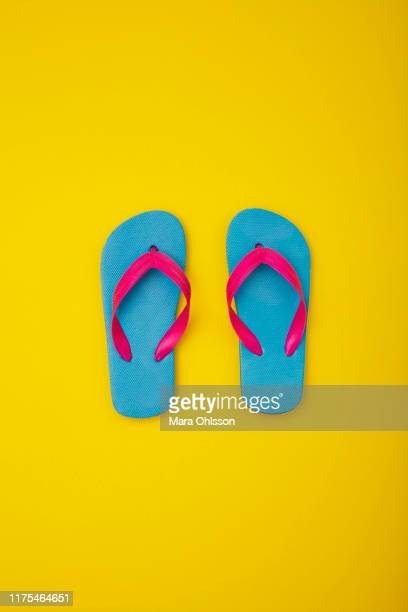 pair of colourful flip-flops on sandy beach - ciabatta infradito foto e immagini stock