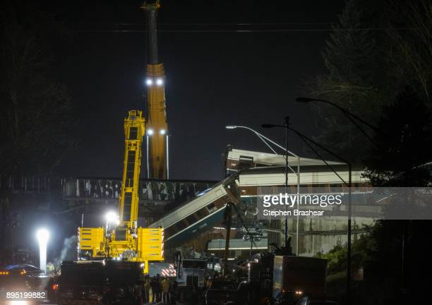 A pair of cranes clear southbound I5 lanes at the scene of an Amtrak train derailment on December 18 2017 in DuPont Washington At least six people...