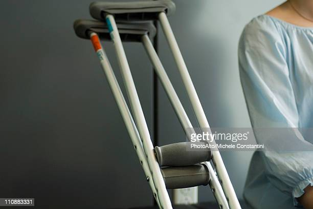 pair of crutches resting beside seated patient - crutches stock photos and pictures