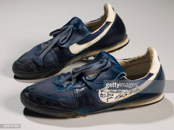 Pair of dark blue Nike athletic shoes worn by African-American professional baseball and football player Bo Jackson . The shoes have white accents...