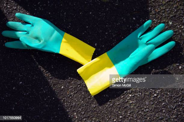 a pair of discarded rubber washing up gloves on a city sidewalk - ゴム手袋 ストックフォトと画像