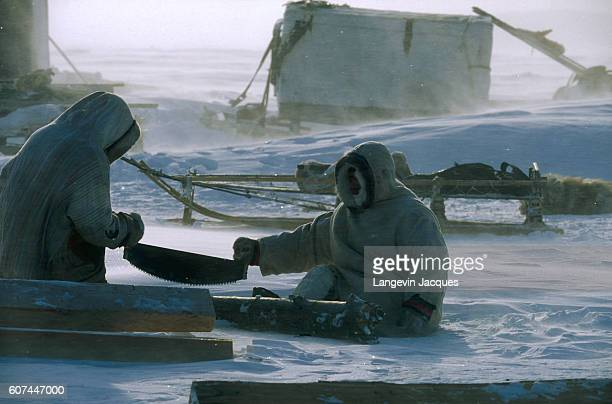 A pair of Dolgans saw wood in their camp near the village of Syndassko Russia The Dolgans traditionally a nomadic people who live along the Taymyr...