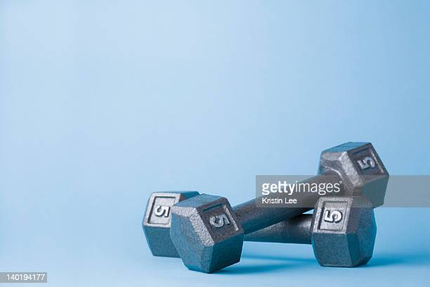 pair of dumbbells on blue background - hand weight stock pictures, royalty-free photos & images