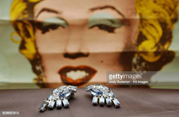 Pair of earclips owned by Marilyn Monroe in front of an original 1971 Marilyn Monroe/Warhol Tate Exhibition poster at Cooper Owen galleries in...