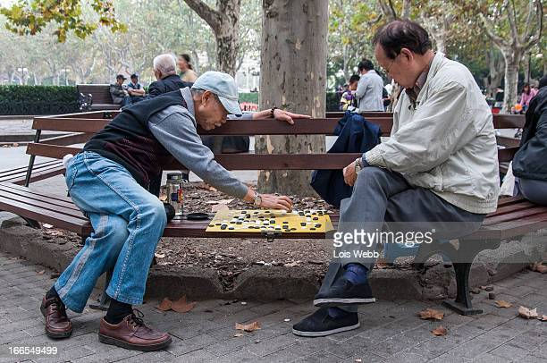 Pair of elderly friends play Chinese drafts on a bench in Fuxing Park in Luwan district , Shanghai