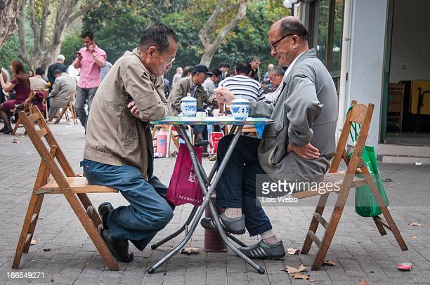 Pair of elderly friends spend the afternoon drinking tea and playing Chinese drafts in Fuxing Park, Luwan District of Shanghai