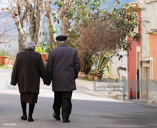 pair of elders walking cojidos of the hand - old women in pantyhose stock photos and pictures