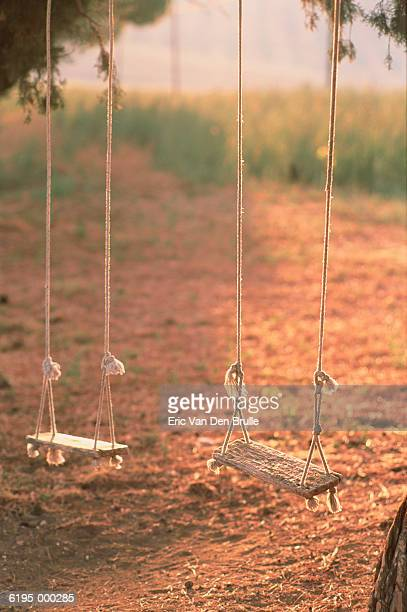pair of empty swings - eric van den brulle stock pictures, royalty-free photos & images