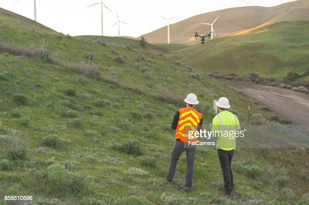 a pair of engineers use a drone to inspect wind farms and power plants in the country - remote control helicopter stock photos and pictures