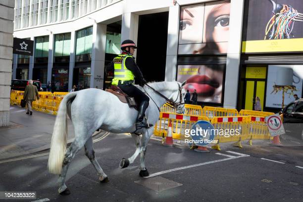 A pair of eyes and a mounted City police officer on Fenchurch Street in the heart of the capital's financial district on 25th September 2018 in...
