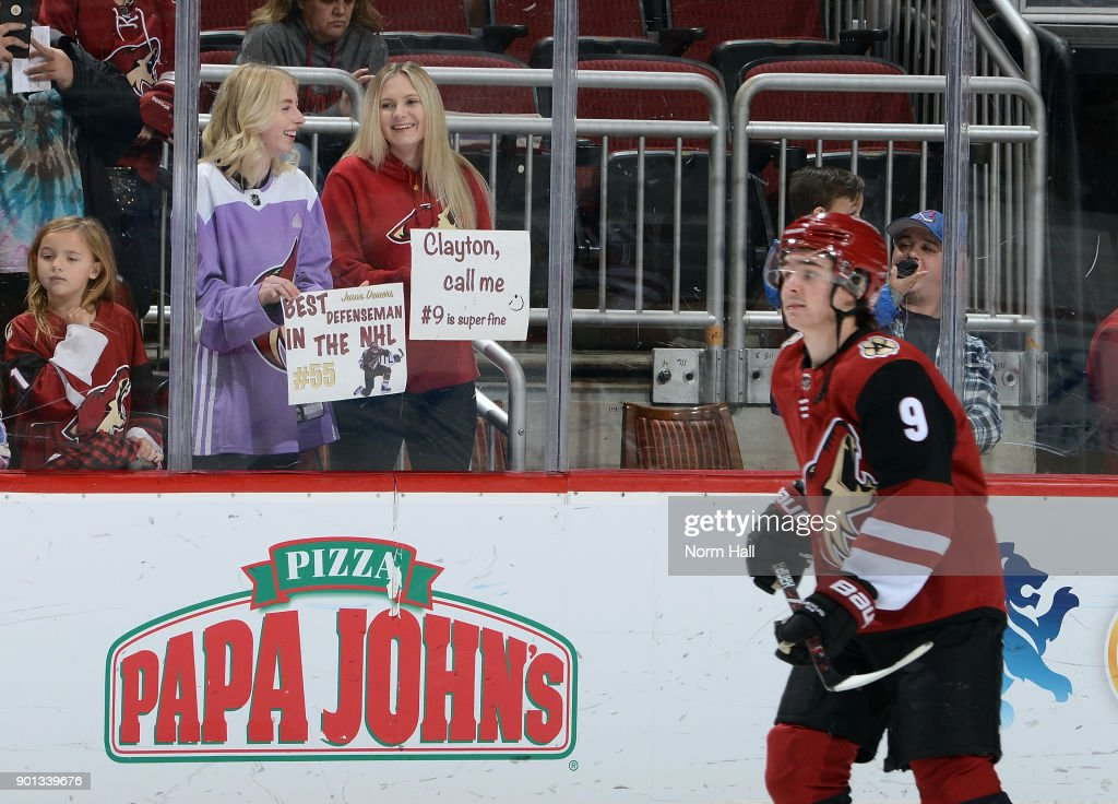 A pair of fans hold up signs for Jason Demers #55 and Clayton Keller #9 of the Arizona Coyotes prior to a game against the Nashville Predators at Gila River Arena on January 4, 2018 in Glendale, Arizona.
