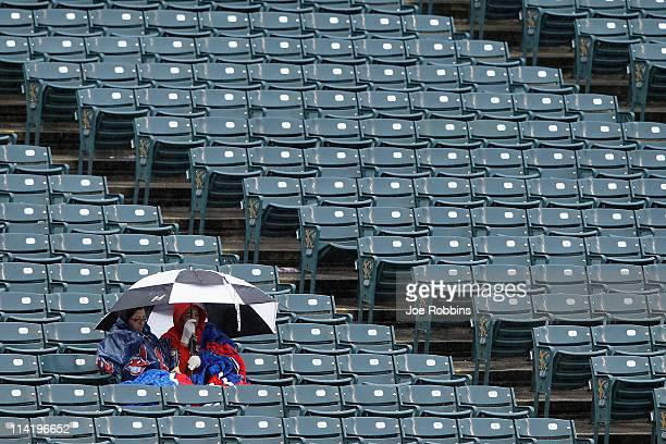 A pair of fans sit in the stands under an umbrella during a rain delay before the game between the Cleveland Indians and the Seattle Mariners at...