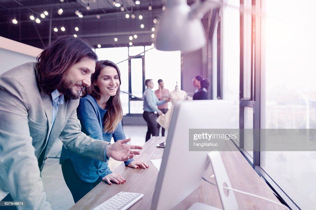 Pair of fashion designers discussing ideas in design studio environment : Stock Photo
