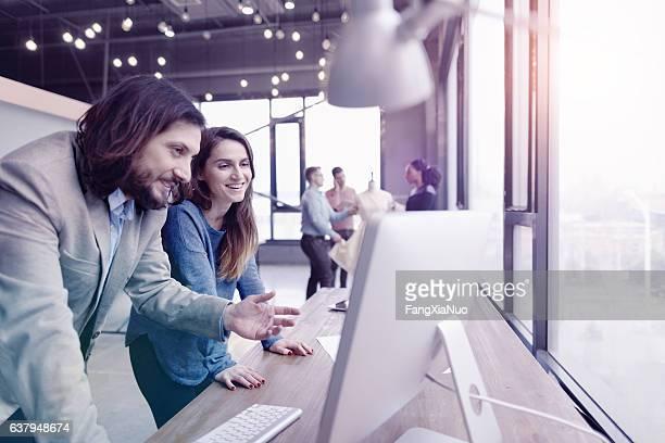 Pair of fashion designers discussing ideas in design studio environment