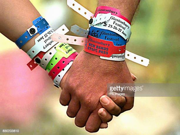 A pair of festivalgoers with numerous wristband passes at the Glastonbury festival