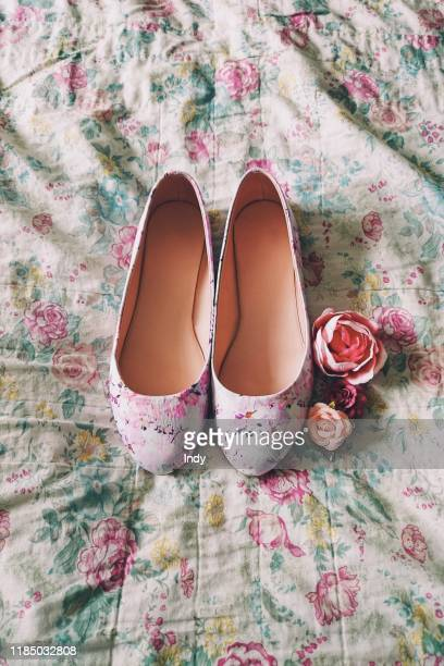 pair of flat floral pumps on floral bed sheet with flowers - pump dress shoe stock pictures, royalty-free photos & images