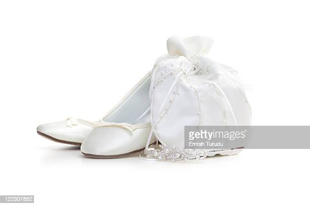 pair of flat white satin shoes and tiara on white - white satin stock photos and pictures