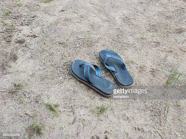 a pair of flip flops on a beach - heshphoto imagens e fotografias de stock