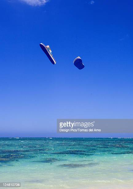 A pair of flipflops flying through the air above turquoise ocean.