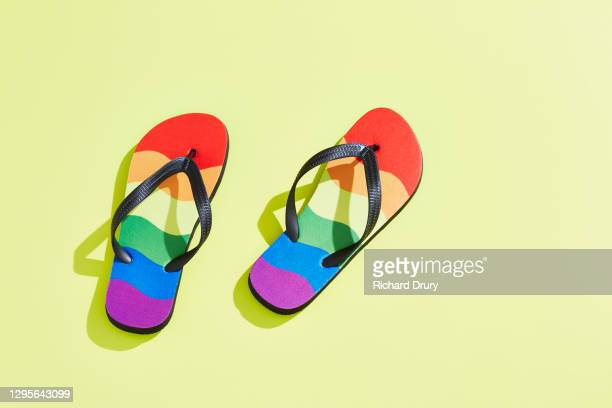 a pair of flip-flops in the design of the lgbtqi pride flag - richard drury stock pictures, royalty-free photos & images