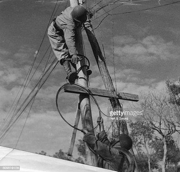 A pair of French Moroccan signalmen fixing telephone communication wires to a telegraph pole France