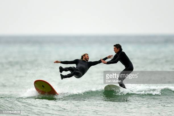 Pair of friends surf together at Fistral Beach on May 04, 2020 in Newquay, England. The country continued quarantine measures intended to curb the...