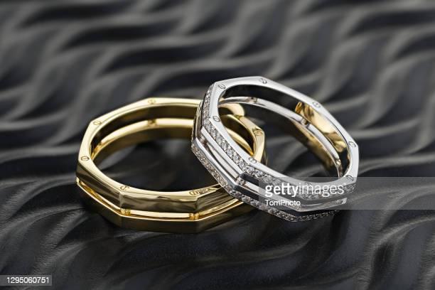 pair of geometric shape wedding rings with diamonds on black background - ホワイトゴールド ストックフォトと画像